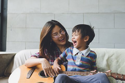 Woman in glasses playing guitar with son