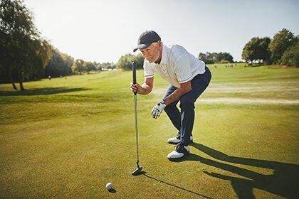 older man lining up golf shot